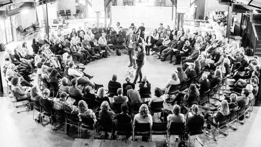 Viser en ring med deltakere i oppstarten av en Open Space-samling